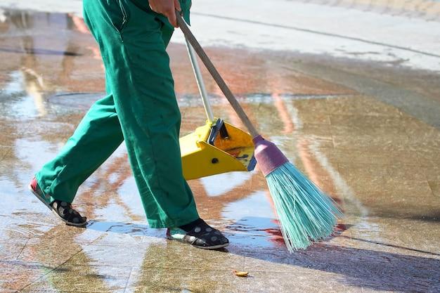 O zelador limpa a calçada da cidade de folhas caídas
