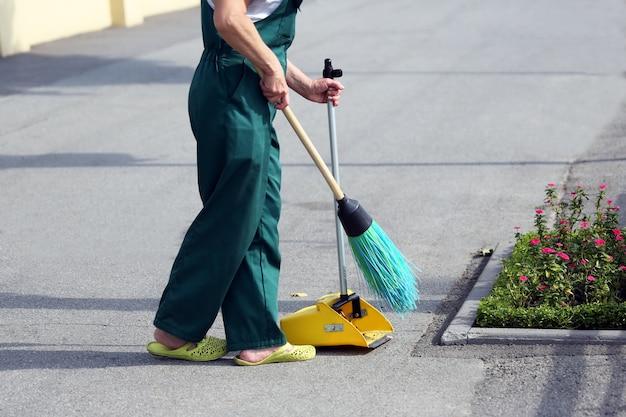 O zelador varrendo a rua das vassouras
