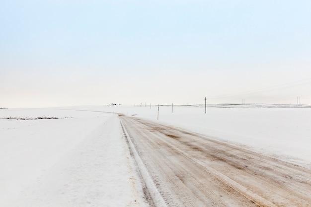 Oad no inverno fotografou o close up da estrada para o movimento de veículos cobertos de neve, temporada de inverno, campo, estrada vazia