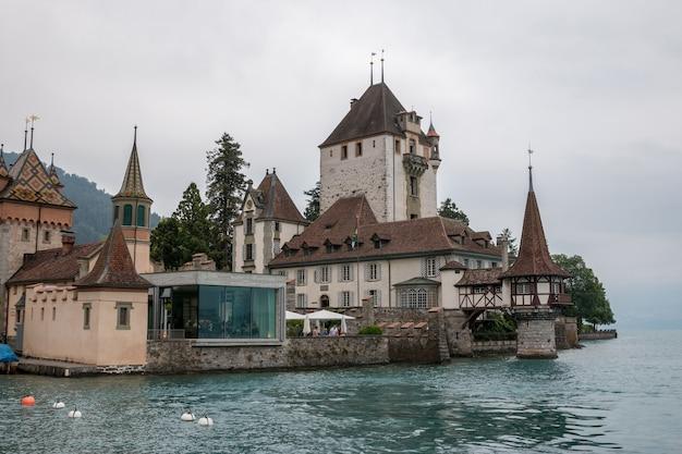 Oberhofen, suíça - 24 de junho de 2017: vista no castelo oberhofen - museu vivo e parque do navio, suíça, europa. paisagem de verão, clima ensolarado, céu azul e dia ensolarado