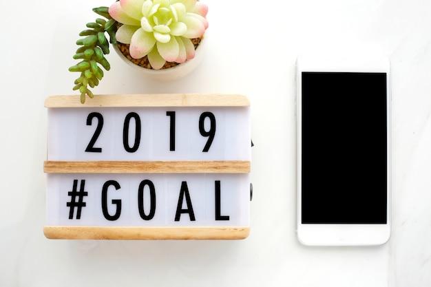 Objetivo de 2019 na caixa de madeira e telefone inteligente com em branco na tela na mesa de escritório
