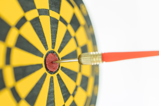 Objetivo, planejamento e conceito de alvo. close-up de dardos vermelhos no centro da placa de dardo preto e amarelo