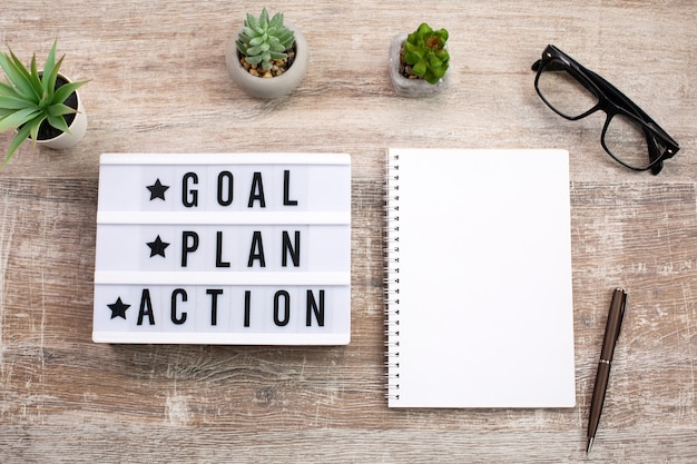 Objetivo, plano, texto de ação na caixa de luz e notebook