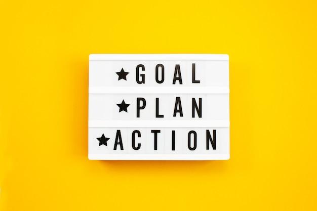 Objetivo, plano, texto de ação na caixa de luz sobre fundo amarelo.