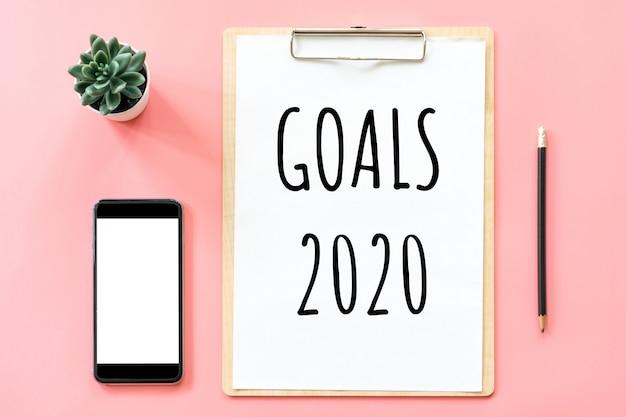 Objetivos 2020 e artigos de papelaria com prancheta em branco e smartphone