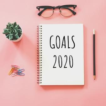 Objetivos 2020 e bloco de notas e artigos de papelaria em rosa pastel