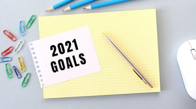 Objetivos 2021 é escrito em um pedaço de papel que está em um caderno ao lado de materiais de escritório. conceito de negócios.