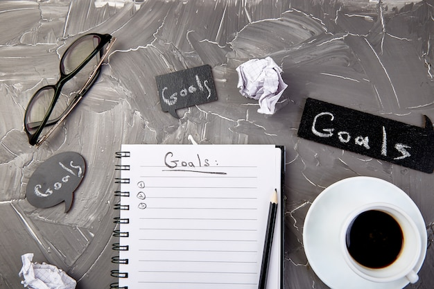 Objetivos como memorando no caderno com a idéia, papel amassado, xícara de café