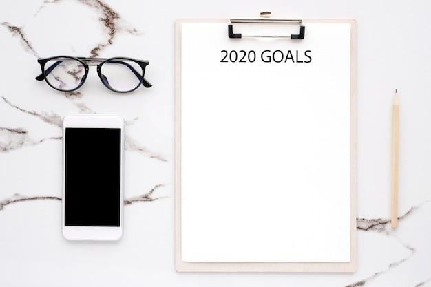 Objetivos de 2020 em papel de nota em branco, com espaço de cópia de texto e telefone inteligente com tela em branco sobre fundo branco de mármore