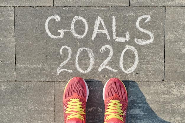 Objetivos de 2020, escritos na calçada cinza com pernas de mulher no tênis