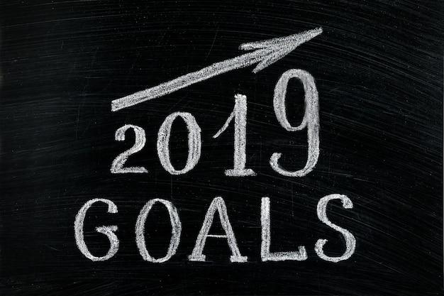 Objetivos do ano novo 2019 com um giz de texto seta ascendente em um quadro negro
