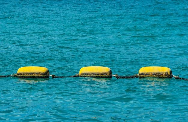 Objeto amarelo flutuando no mar como aviso para a área de perigo.