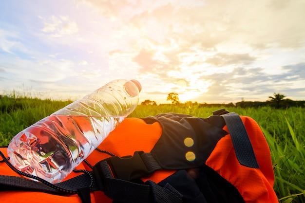 Objeto da trouxa com a garrafa de água na opinião do por do sol e da grama verde.