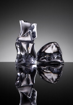 Objeto de cristal de três cubos de gelo com água no fundo do espelho
