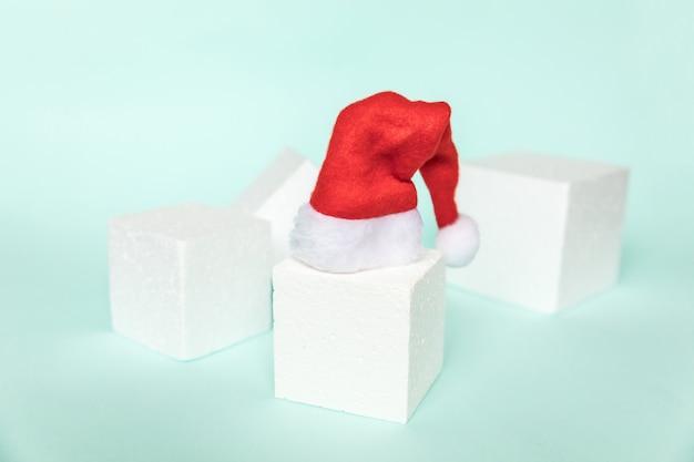 Objeto de inverno de composição simplesmente mínima chapéu de papai noel e formas de cubo forma geométrica pódio isolado