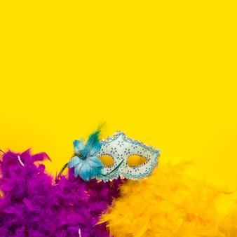 Objetos de carnaval colorido plana leigos sobre fundo amarelo, com espaço de cópia