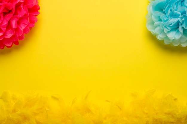 Objetos de carnaval colorido sobre fundo amarelo, com espaço de cópia