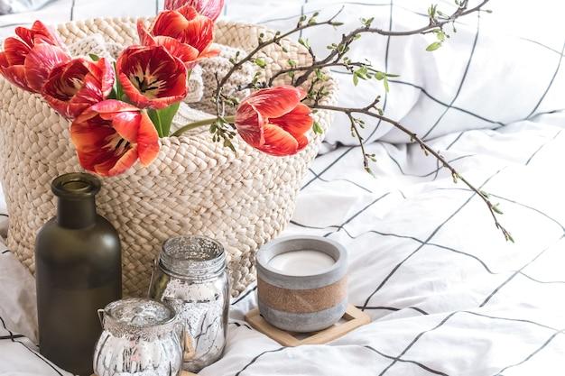 Objetos de decoração aconchegante para casa no interior da sala. com lindas tulipas vermelhas. o conceito de decoração e atmosfera doméstica
