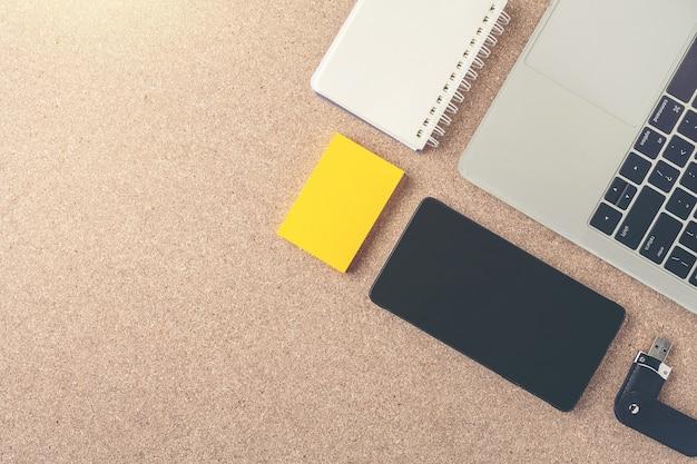 Objetos de empresários colocados no chão de madeira marrom.