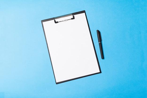 Objetos de escritório em branco organizados para apresentação da empresa em fundo de papel azul