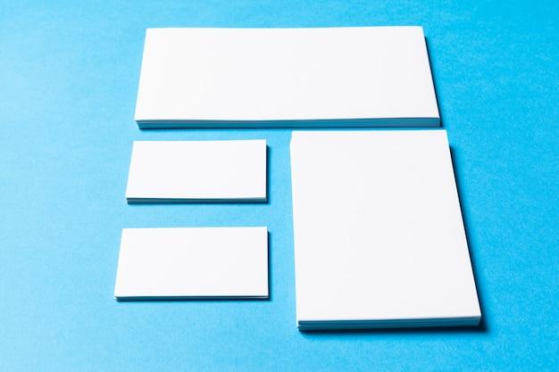 Objetos de escritório em branco organizados para apresentação da empresa em papel azul
