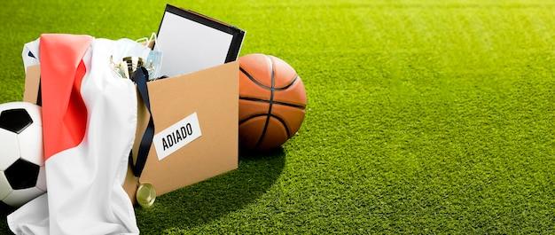 Objetos de evento esportivo adiados em caixa com espaço para texto