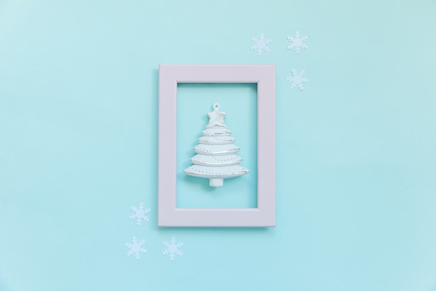 Objetos de inverno de composição simplesmente mínima árvore de abeto em moldura rosa isolada em fundo azul
