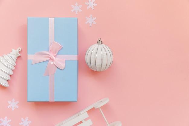Objetos de inverno de composição simplesmente mínima enfeite caixa de presente isolada em fundo rosa