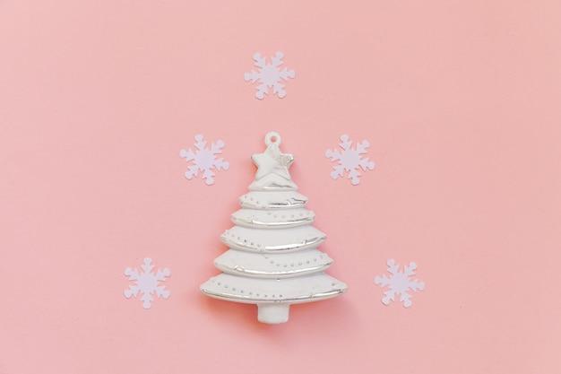 Objetos de inverno enfeitam flocos de neve de pinheiro isolado em fundo rosa