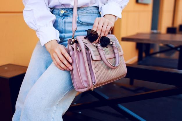 Objetos de moda. as mãos da mulher com bolsa e óculos de sol. garota fashion sentado ao ar livre. jeans elegantes.