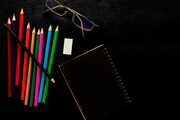 Objetos de negócios de lápis, nota de papel e óculos no fundo de couro preto