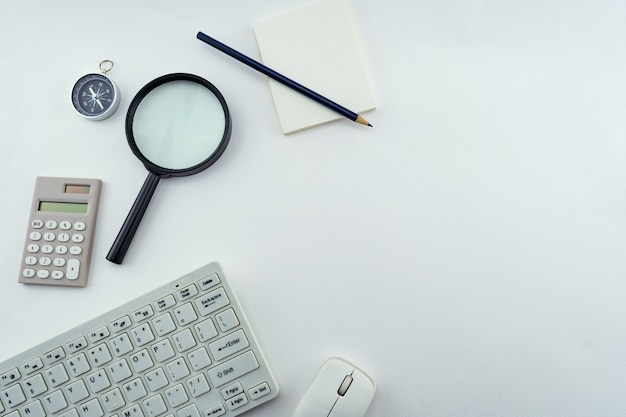 Objetos de negócios de pc, teclado, mouse, lápis, bússola e calculadora, lupa no fundo da mesa branca.