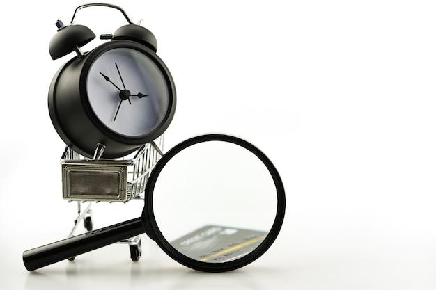 Objetos de negócios de venda de verão de carrinho de compras com lupa, despertador e espaço de cópia de cartão de crédito para o seu texto.