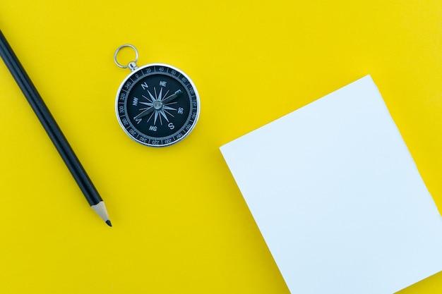 Objetos de negócios de vista superior de papel branco, lápis e bússola na papelada fundo amarelo composição plana leiga.