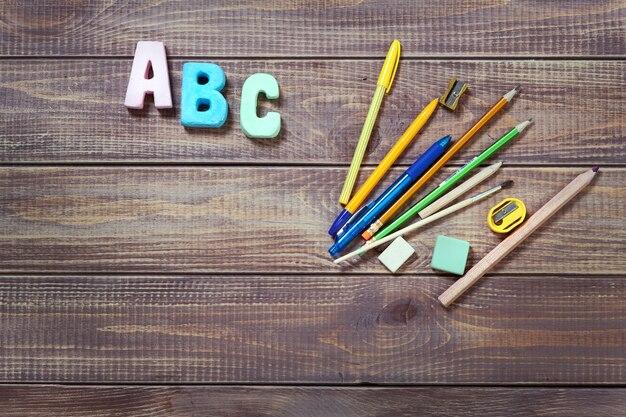 Objetos de papelaria com a palavra abc em fundo de madeira