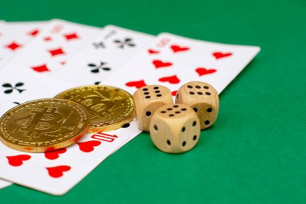 Objetos de um jogo de poker - cartões de jogo, dados de jogo e bitcoins de ouro sobre um fundo verde