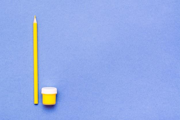 Objetos para desenhar lápis amarelo e guache amarelo em um azul