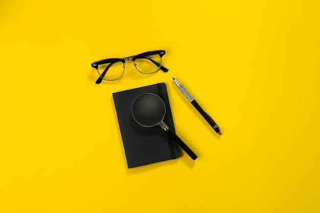 Objetos pretos do escritório em um fundo amarelo. trabalho e criatividade. imagem de cabeçalho do herói do conceito de mídia social. vista do topo. ainda vida. copie o espaço