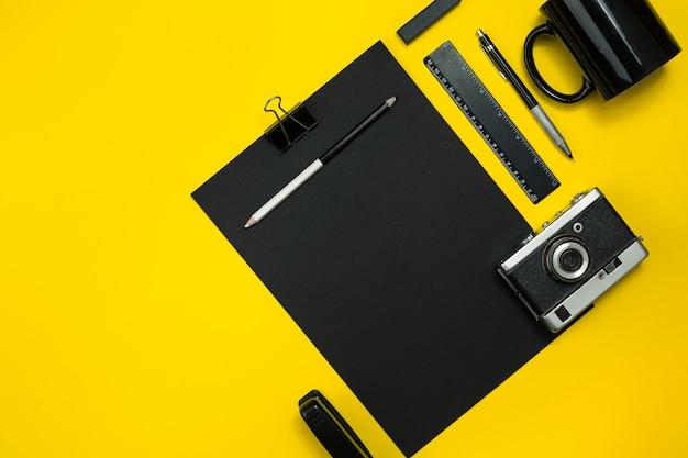 Objetos pretos do escritório em um fundo amarelo trabalho e criatividade vista superior