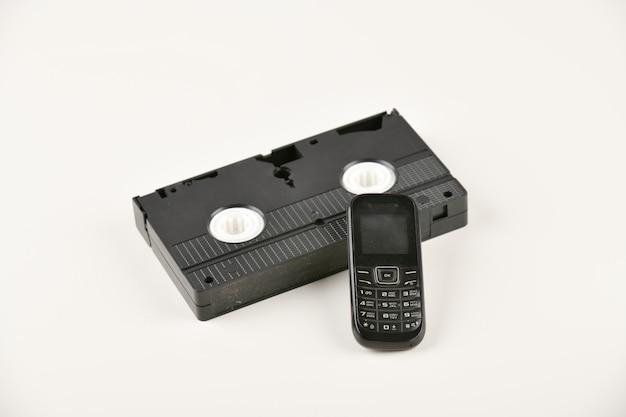 Objetos retrô em um fundo branco. telefone com botão de pressão e cassete de vídeo. tecnologia de mídia analógica do passado. copie o espaço