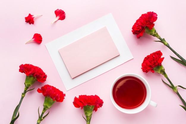 Objetos vermelho-rosa. o copo do chá, cravo floresce o bloco de notas para o texto no fundo do rosa pastel.