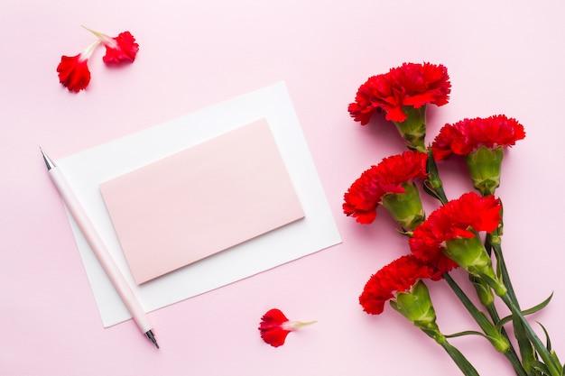 Objetos vermelho-rosa. xícara de chá, cravo flores bloco de notas para texto em fundo rosa pastel. copie o espaço. vista superior