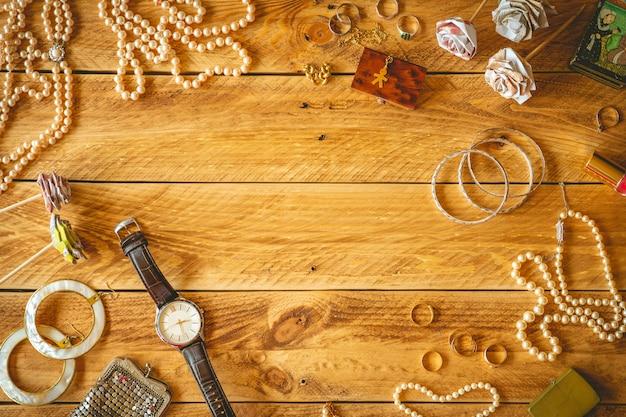 Objetos vintage e joias em uma mesa de madeira com espaço de cópia no meio.