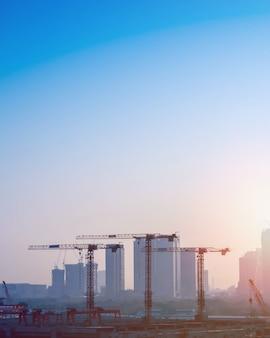 Obra de construção com guindastes no fundo skycrapers