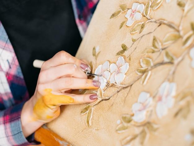 Obra em andamento. inspiração. artista de mulher com ferramenta. tela sobre cavalete. textura de padrão de flores e pássaros.
