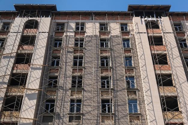 Obras de acabamento em mármore em fachada de prédio alto