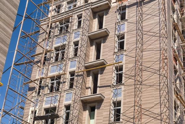Obras de acabamento na fachada de um novo edifício residencial