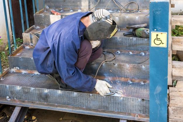 Obras de construção um soldador macho faz um dispositivo de elevação para deficientes