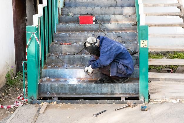 Obras de construção um soldador masculino faz um dispositivo de elevação e uma escada para pessoas com deficiência