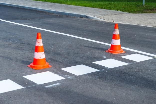 Obras na estrada adiante, cone de plástico laranja avisando sobre novas linhas de estrada.
